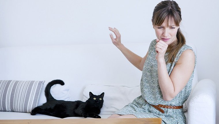 A woman sitting next to a black cat raises her hand to cover a sneeze.