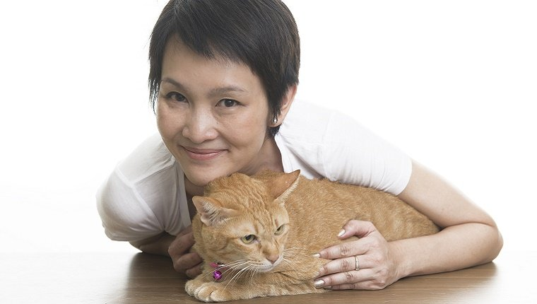 A woman leans over and holds an orange cat on a table in front of a white background.