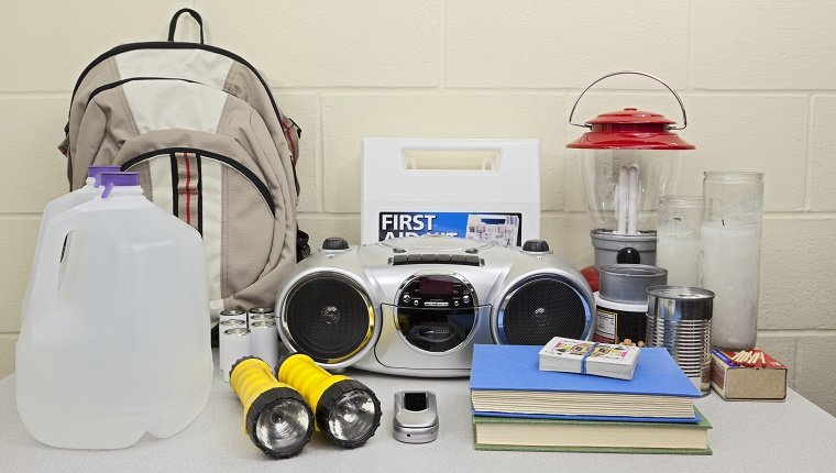 A disaster emergency kit with water, flashlights, a radio, a phone, and other supplies.