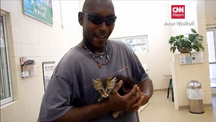 Frazier holds the kitten in his hands at the shelter