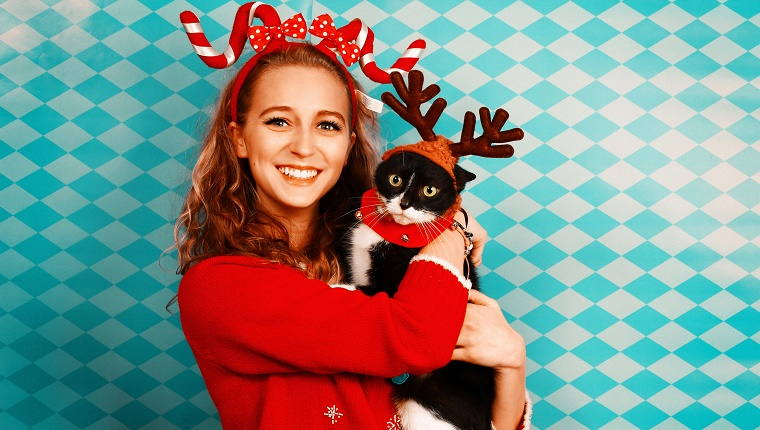 A girl posing for a Christmas card wearing a candy cane head band holding a black cat wearing moose antlers.