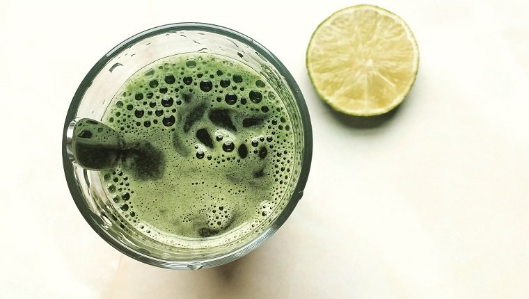 Directly Above Shot Of Spirulina Drink In Glass By Lemon On Table