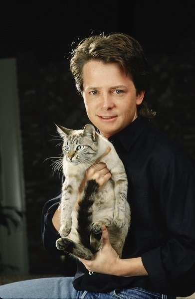 "BEVERLY HILLS, CA - 1988: Actor Michael J. Fox poses with his cat during a 1988 Beverly Hills, California, photo portrait session. Fox, a three-time Emmy Award winner for his work on TV's ""Family Ties,"" also starred in the ""Back to the Future"" film trilogy. (Photo by George Rose/Getty Images)"