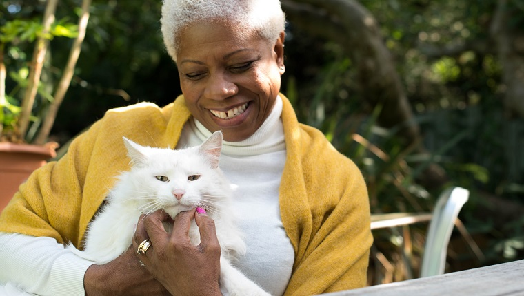 A senior woman sits in the garden cuddling a beautiful white cat.